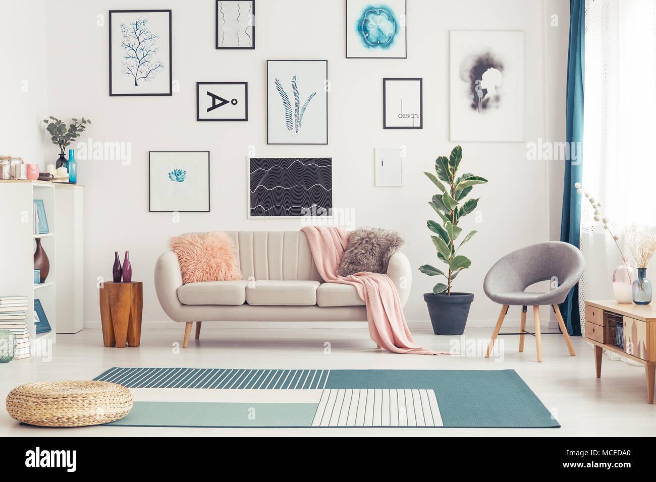 Pouf auf blauen Teppich in geräumigen rosa Wohnzimmer Interieur mit ...