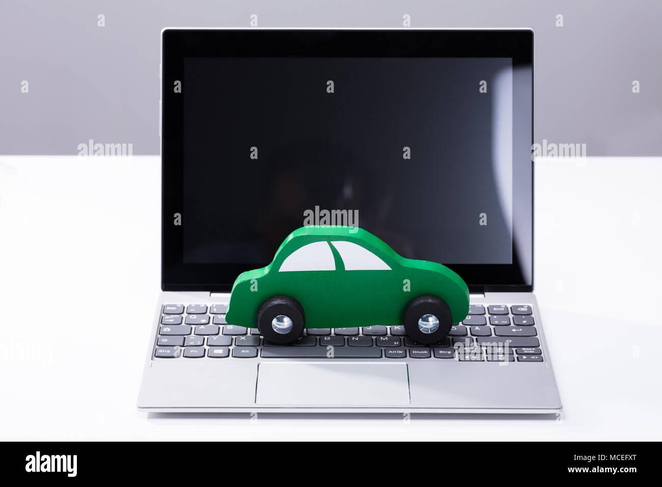 Green Car mit Laptop mit leerer Bildschirm Stockbild