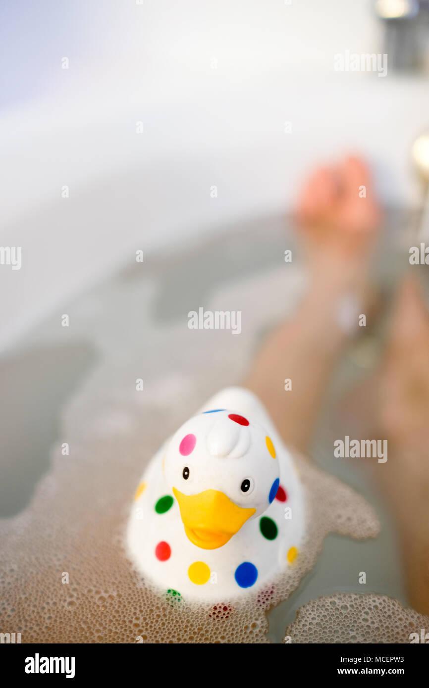 Nahaufnahme der bunt getupft Quietscheentchen in der Badewanne mit Blasen und Beine von jemand sichtbar unter Wasser im Hintergrund Stockbild