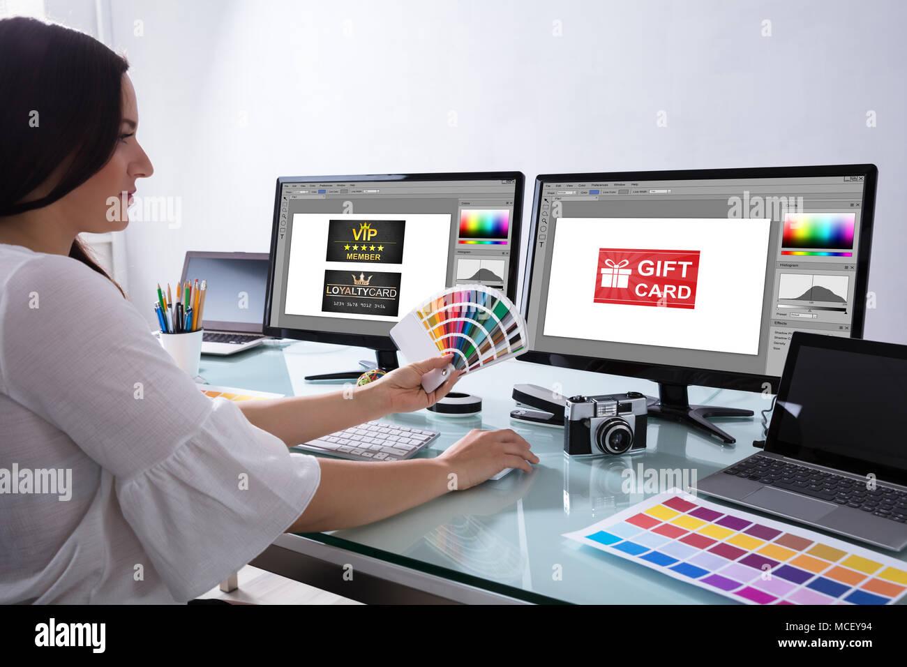 Weibliche Designer Holding Farbmuster Arbeiten mit Geschenkkarte auf Bildschirm Stockbild