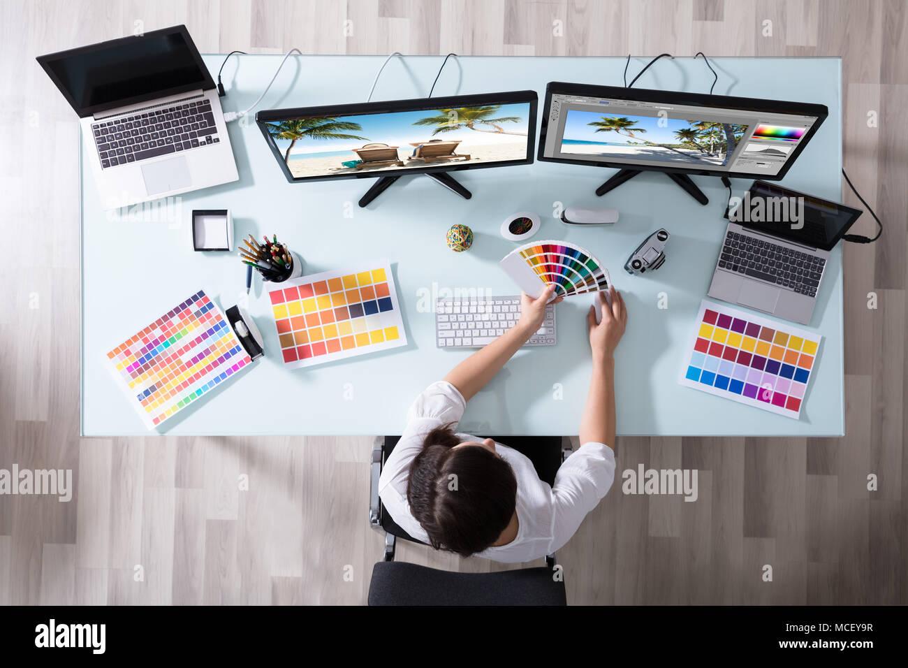 Hohe Betrachtungswinkel eines weiblichen Designer über Farbmuster bei der Arbeit auf mehrere Computer Stockbild