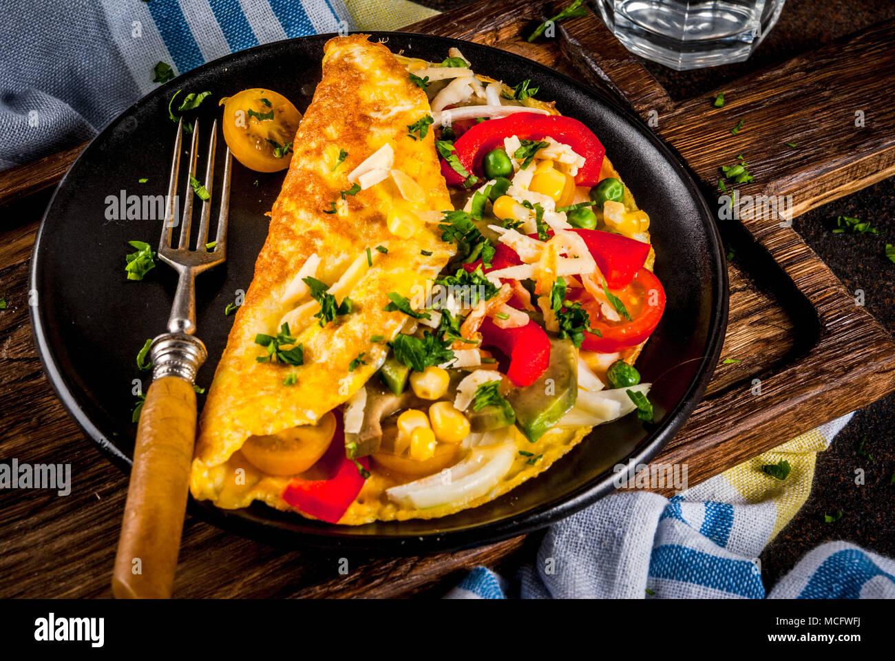 Gesundes Frühstück essen, Gefüllte Eier Omelett mit Gemüse, dunklen konkreten Hintergrund Kopie Raum Stockbild
