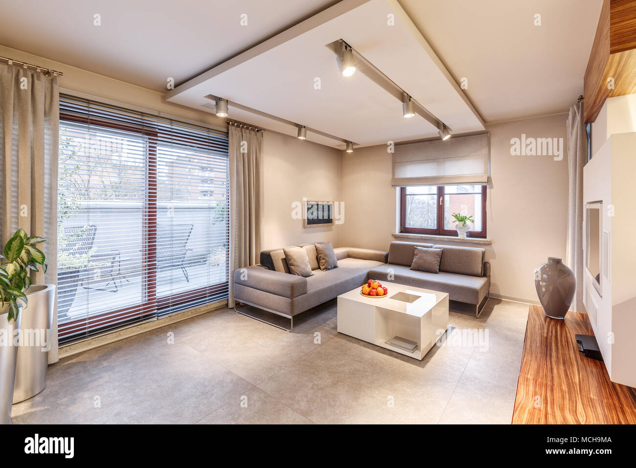 Geräumige, Braun Wohnzimmer Mit Sofa, Tisch, Beleuchtung, Große Schiebetür  Balkon Fenster Und Vorhänge