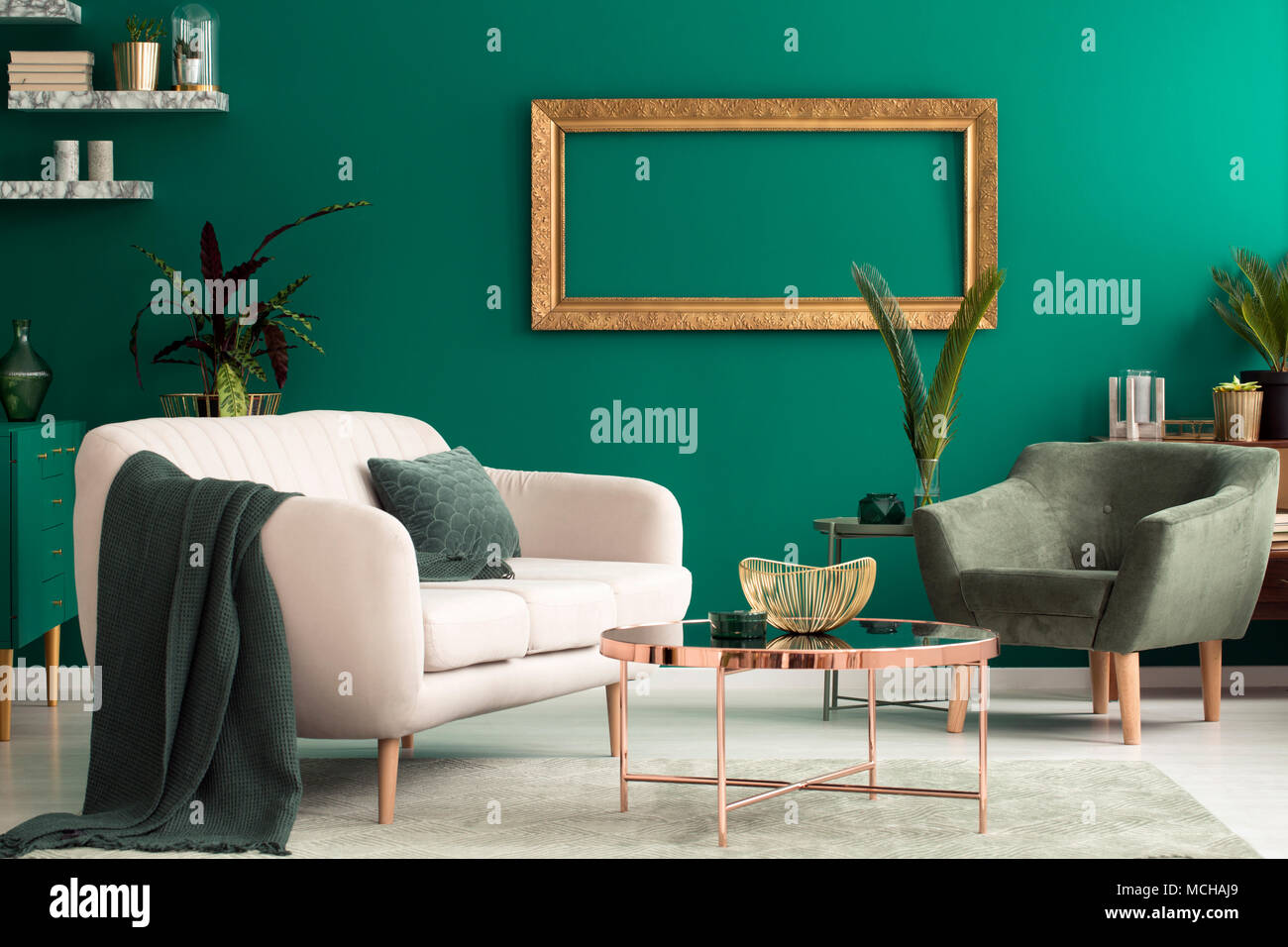 Kupfer Tisch zwischen beige Sofa und Sessel im grünen Wohnzimmer ...