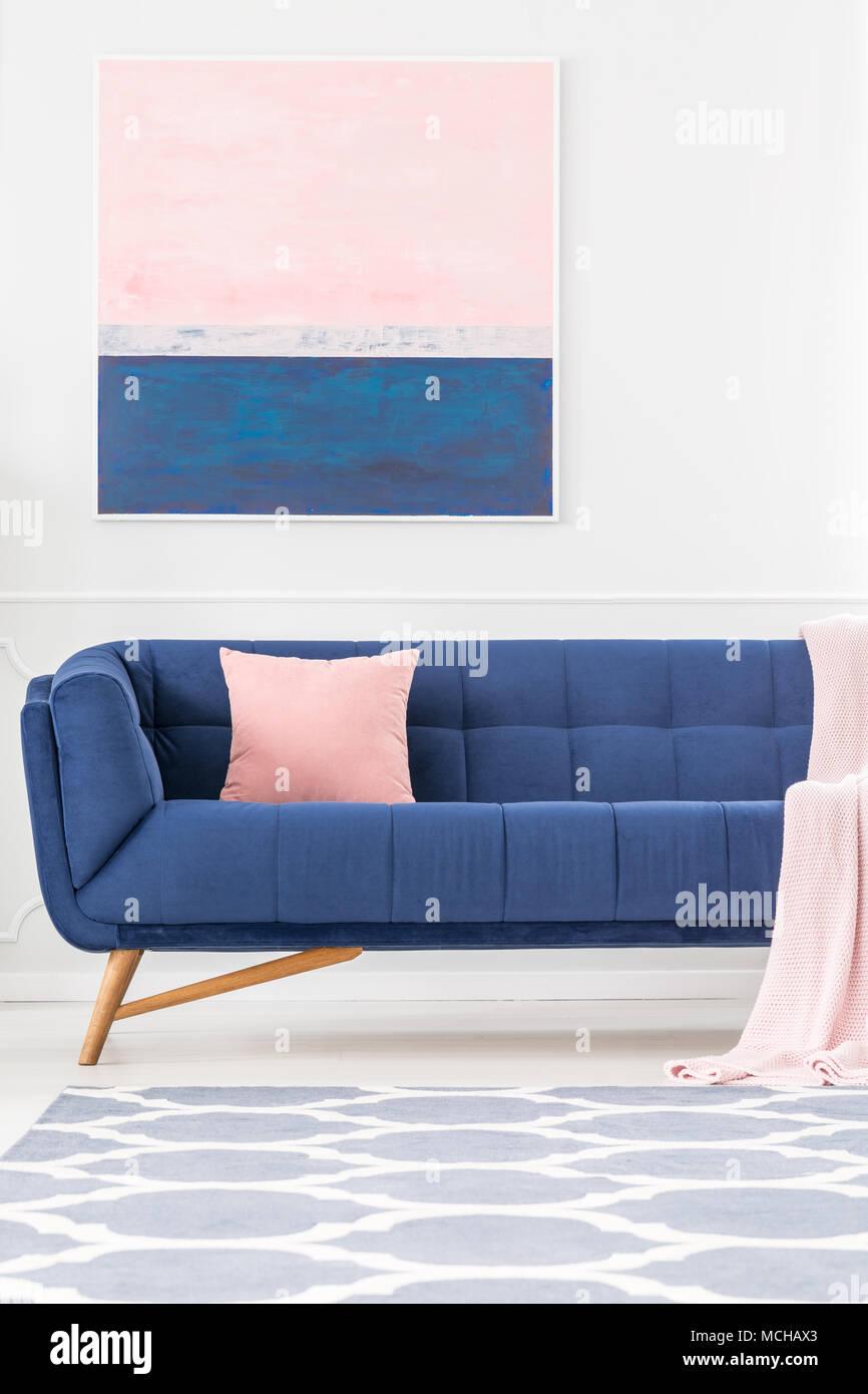 Marine Blaue Couch Mit Rosa Kissen Und Decke Im Wohnzimmer Einrichtung Mit  Gemusterten Teppich Und Gemälde An Der Wand