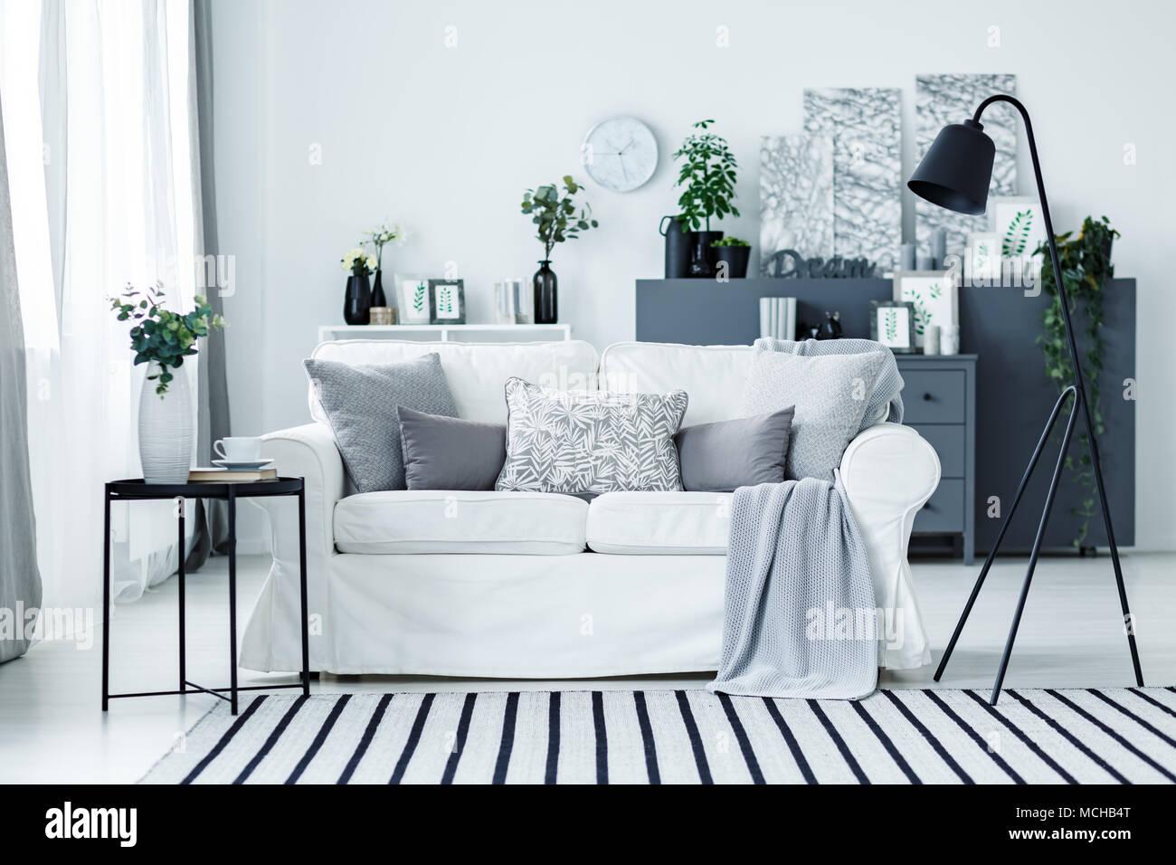Grau Weiß Sofa Mit Kissen Und Decke Im Hellen Wohnzimmer Interieur Mit  Metall Lampe, Frische Pflanzen Und Gestreiften Teppich