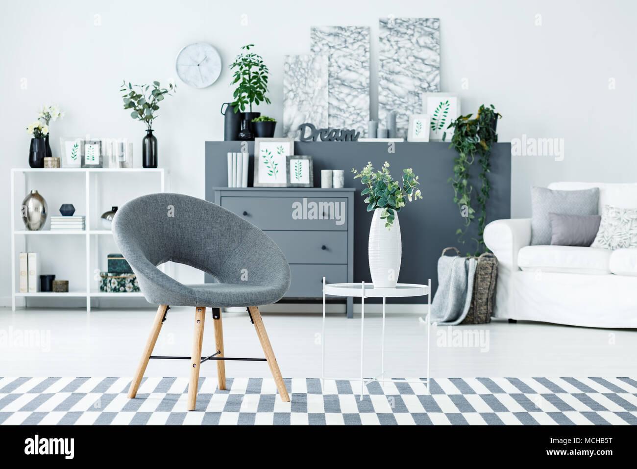 Grau Stuhl und weißes Metall Tisch mit Blumen in Keramik Vase in ...