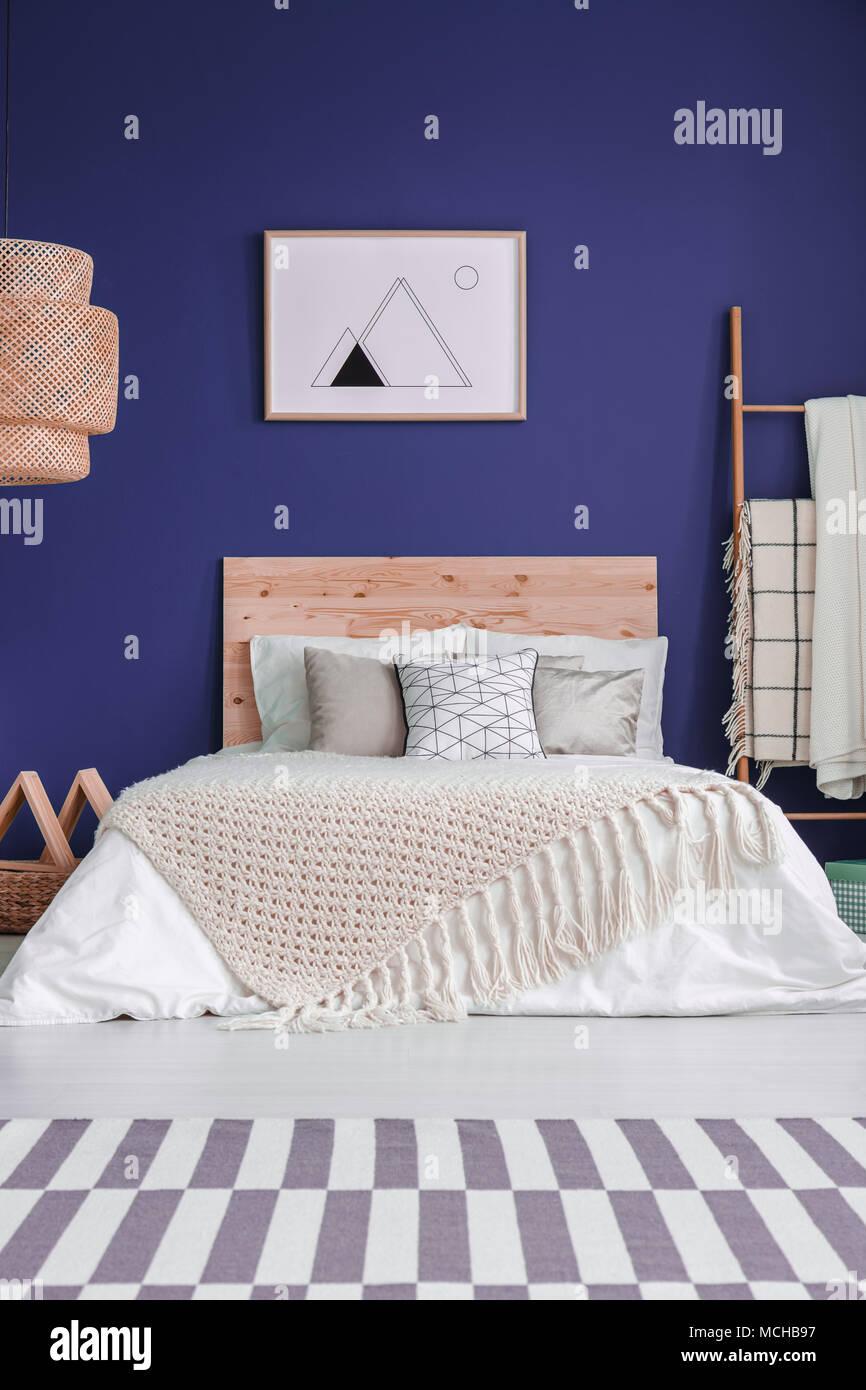 Poster Auf Lila Wand über Dem Bett Mit Hölzernen Bedhead Und Stricken Decke  In Gemütlichen Schlafzimmer Innenraum