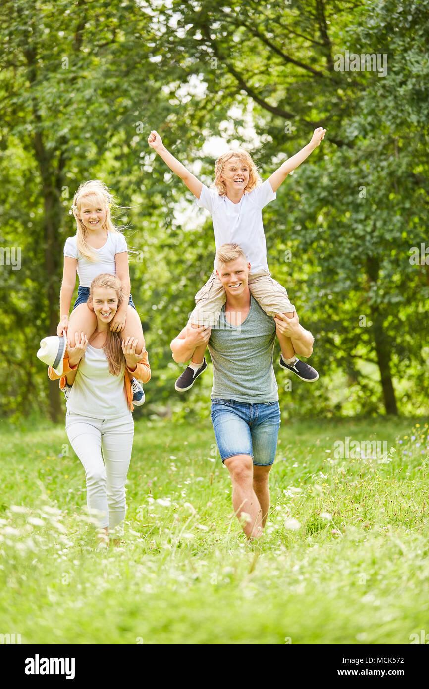 Kinder fahren Huckepack auf dem Rücken der Eltern auf eine Reise Stockbild