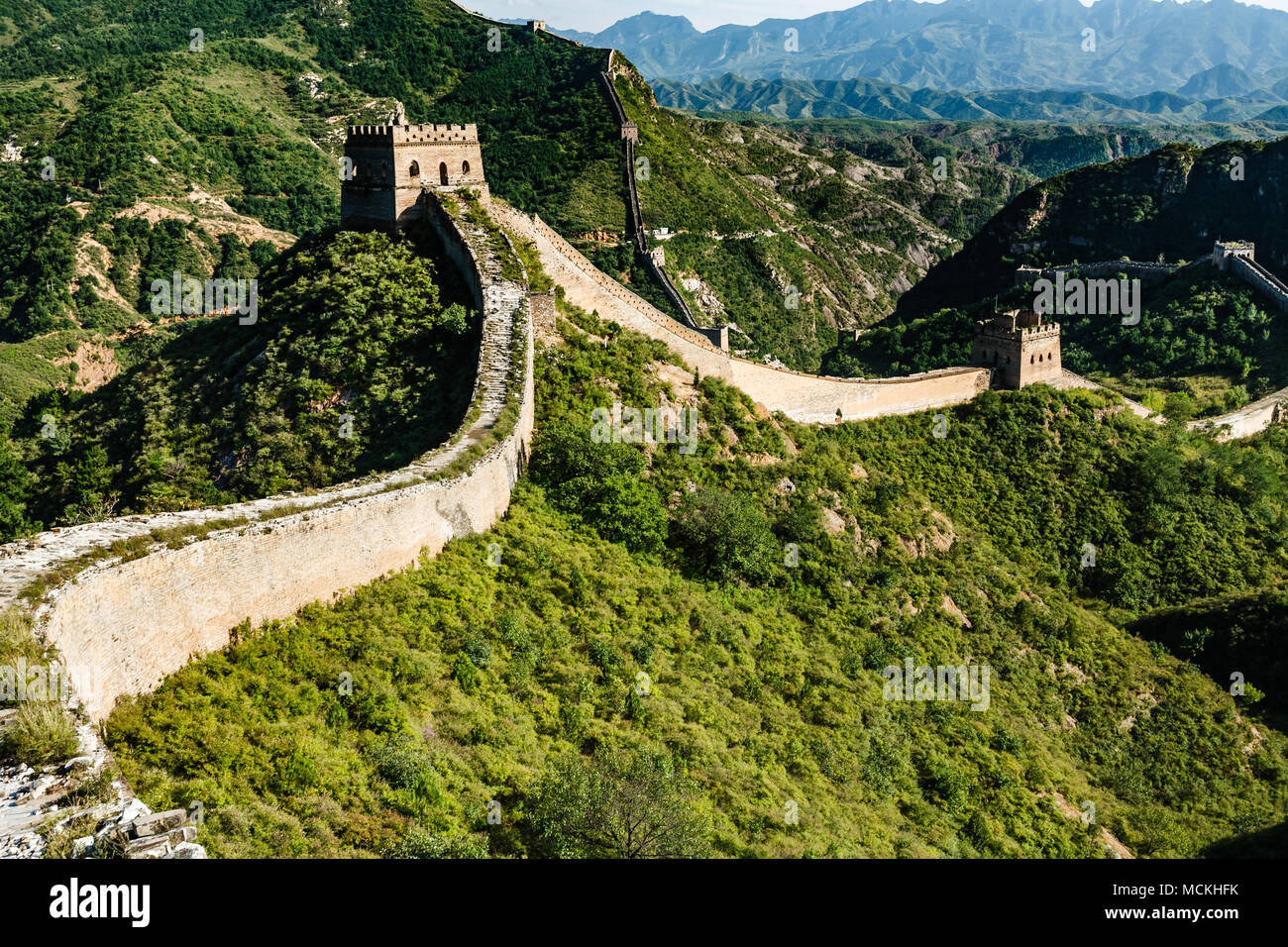Die antike Straße an der Oberseite der Großen Mauer von China nach einem alten Turm, die an der Berge und grüne Landschaft Stockbild