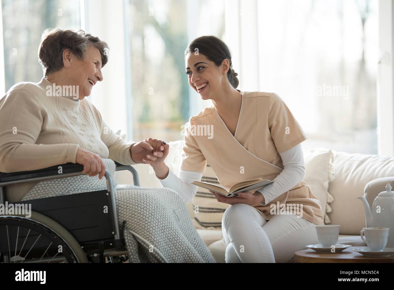 Senior in einem Rollstuhl und schöne Krankenschwester und lächelnd die Hände beim Lesen eines Buches Stockbild
