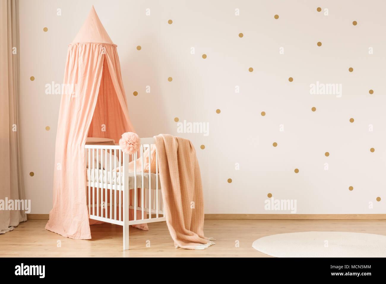 Rosa Decke Auf Weissen Kinderbett Gegen Tapete Mit Gold Punkte In