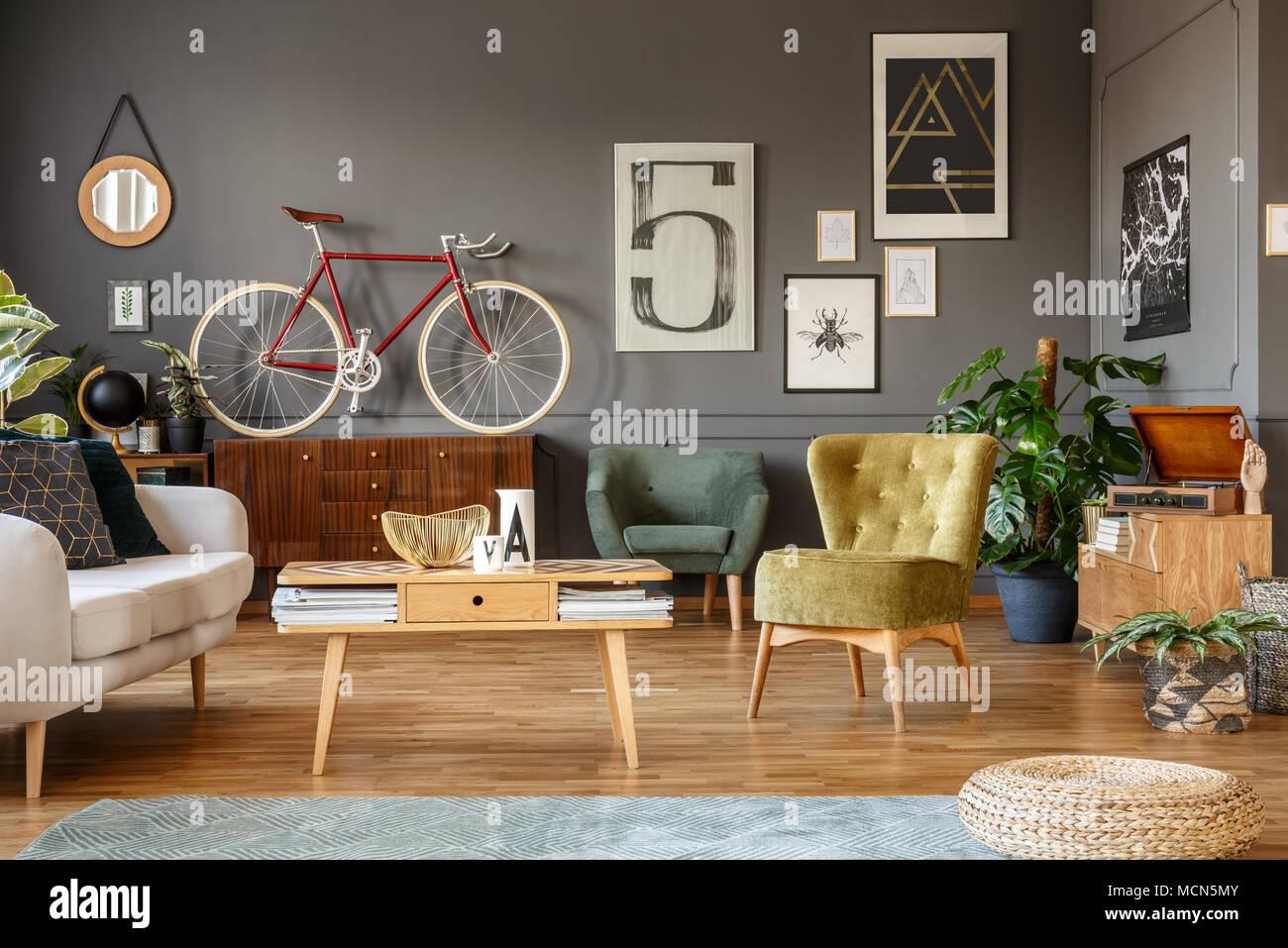 Attraktiv Kunst Sammlung Auf Eine Graue Wand, Holz  Couchtisch, Sessel Und Rote Rad  In Einem Unordentlichen Wohnzimmer Innenraum