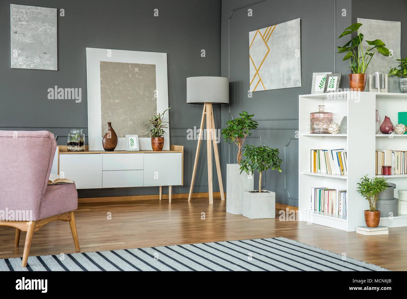 Rosa Sessel In Grau Wohnzimmer Einrichtung Mit Holz Lampe Zwischen Weissen Schrank Und Pflanzen Stockfotografie Alamy