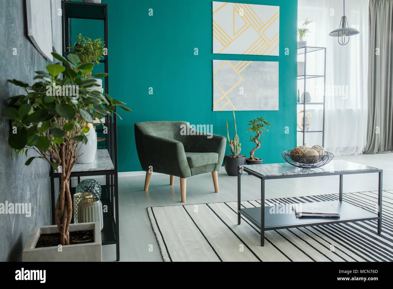 Frische Topfpflanzen In Grün Und Grau Wohnzimmer Einrichtung Mit Sessel Und  Zwei Geometrischen Gemälde