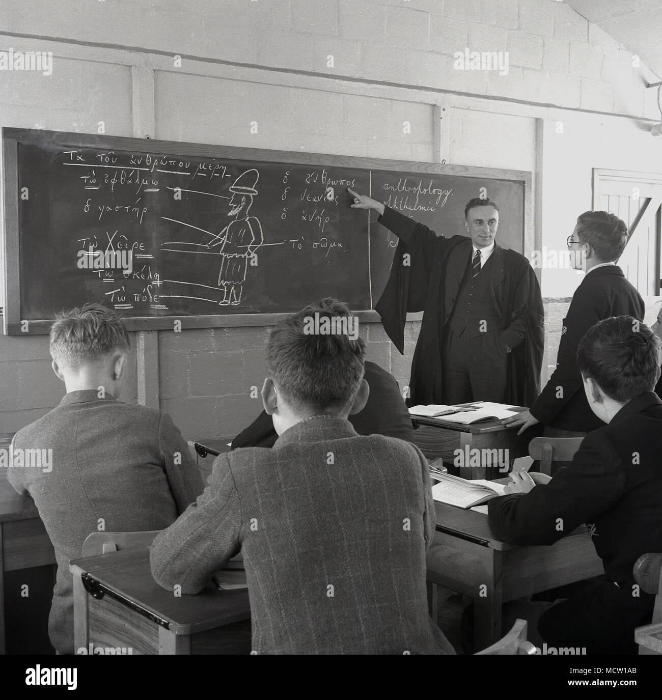 1950er Jahre, historische Bild eines erwachsenen männlichen Lehrer in Hemd und Krawatte und das Tragen eines traditionellen Kleid mit einer großen Tafel zu lehren, eine kleine Gruppe von Schülern am Schreibtisch sitzen, England, UK erziehen oder. Stockfoto