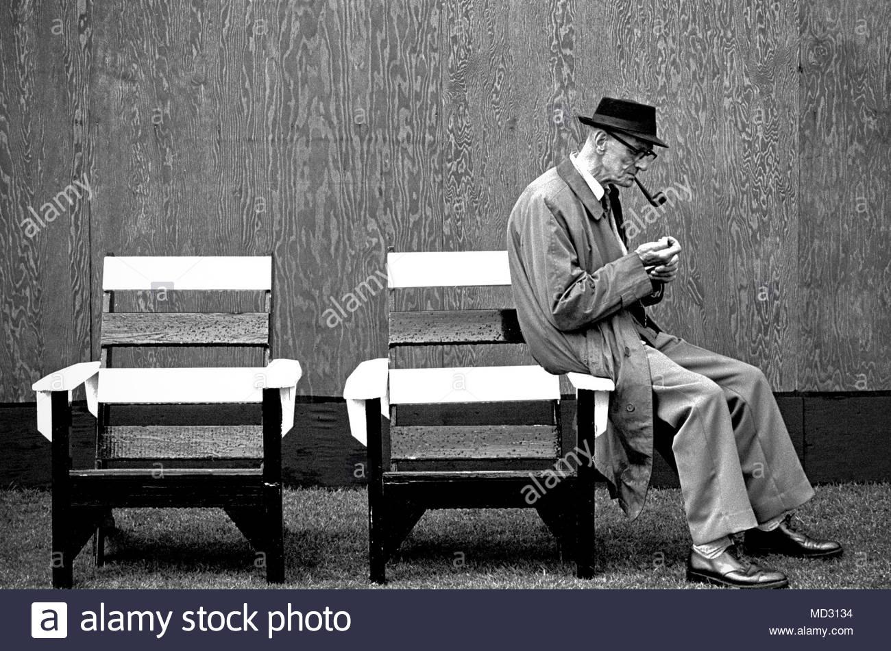 Ältere Mann in einem regenmantel Beleuchtung seine Pfeife, während auf dem Arm von einem sehr nassen Holzbank Art Stuhl in den frühen 80er sat s in North West England, UK Foto DON TONGE Fotograf Stockbild