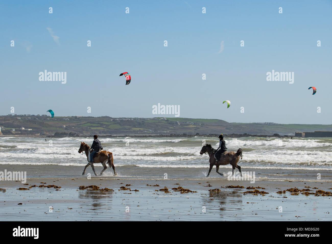 Langen Felsformation, in der Nähe von Marazion, Cornwall, UK. 18. April 2018. UK Wetter. Eine steife onshore Wind hielt die Temperaturen bis zu 19 Grad C heute Mittag am Strand von langen Felsformation. Cornwall schwimmen Pferde für einen Galopp waren, jedoch werden Sie nicht schwimmen, bis das Meer erwärmt sich ein bisschen mehr im Mai. Foto: Simon Maycock/Alamy leben Nachrichten Stockbild