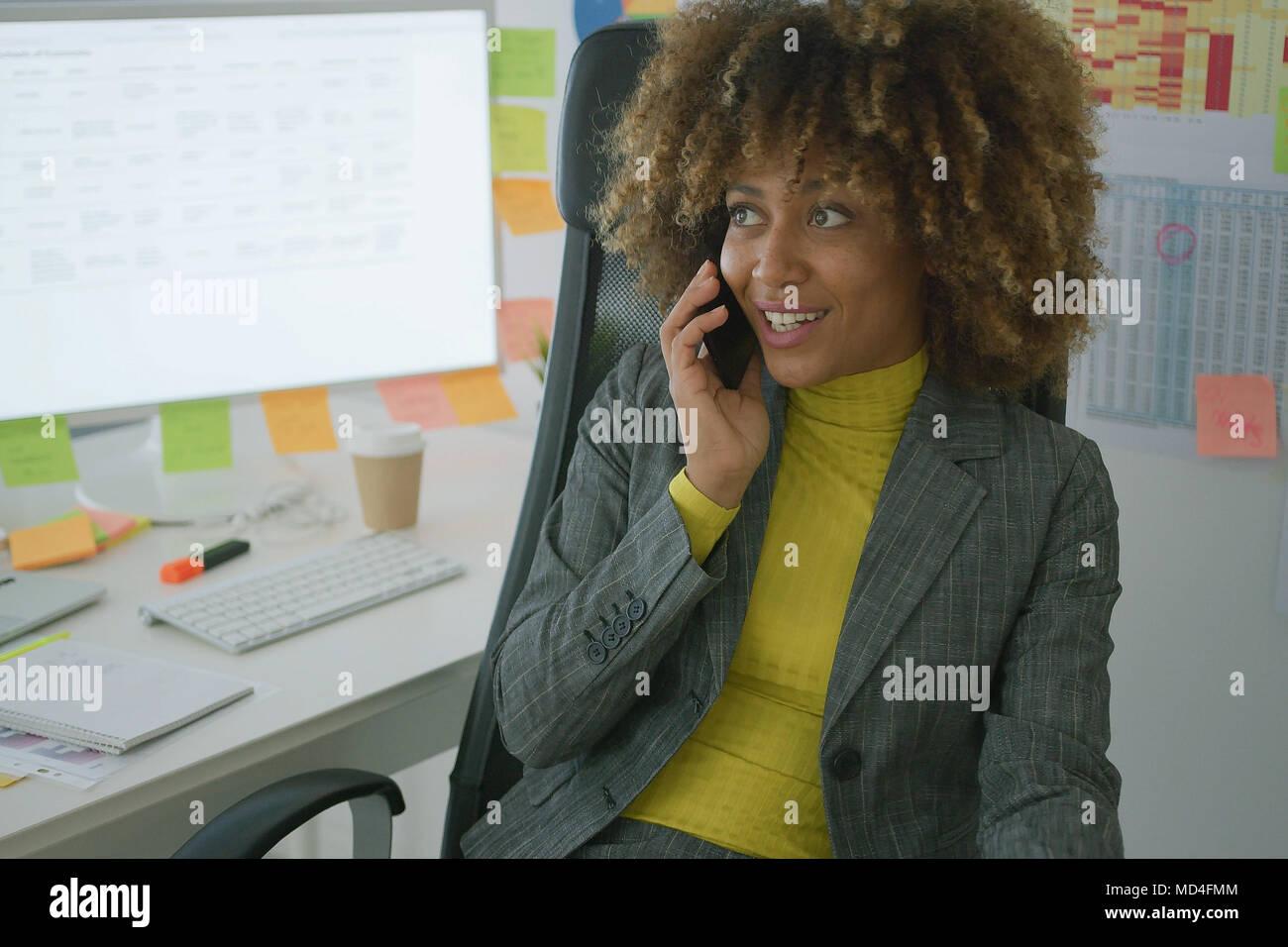 Fröhliche elegante Mitarbeiter am Telefon sprechen Stockbild