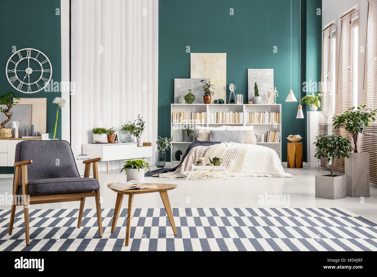 Fantastisch Weiß Bett Gegen Grüne Wand Und Vintage, Grau Sessel Auf Gestreiften Teppich  In Geräumigen Schlafzimmer Innenraum