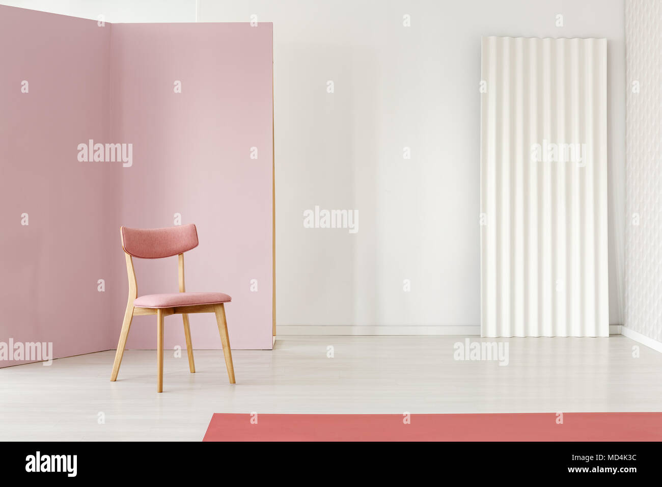 Retro gepolstert holzstuhl durch eine rosafarbene ecke