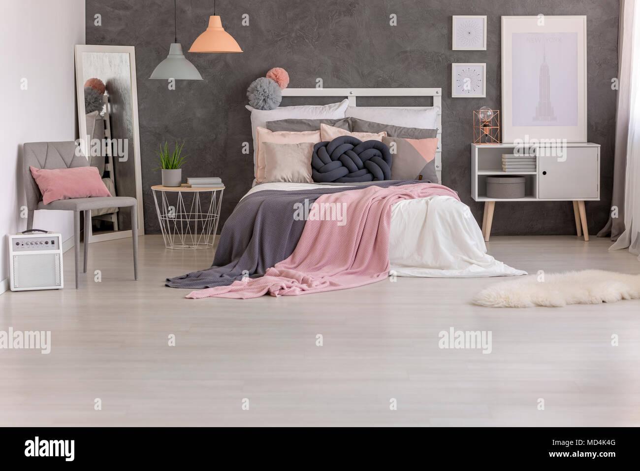 Zwei rosa und grauen Decken auf dem Bett geworfen, mit vielen Kissen ...