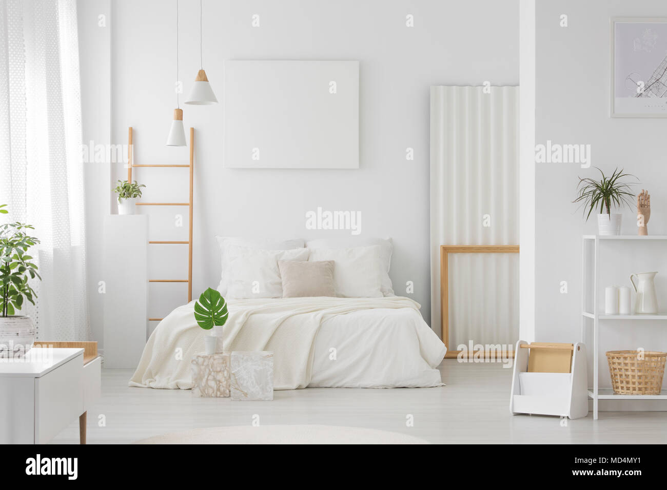 Ein weißes Schlafzimmer mit großem, King Bett, Regale, Leiter und ...
