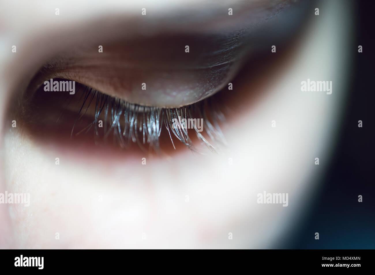 Nahaufnahme der Frau mit langen Wimpern in Trauer nach unten Schauen. Stockbild