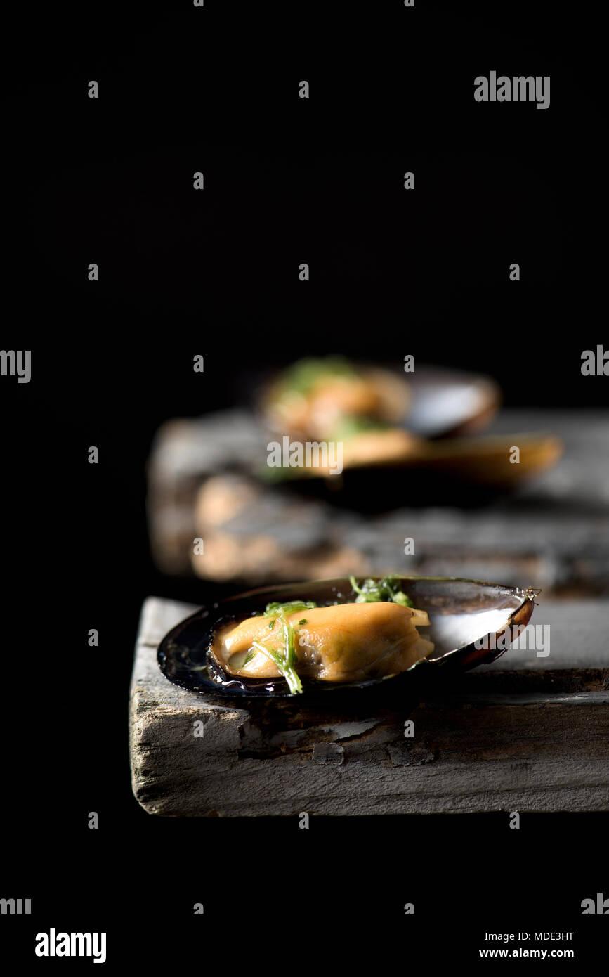 Nahaufnahme von einigen Moules Mariniere, ein französisches Rezept der Muscheln, auf einem rustikalen Holztisch vor einem schwarzen Hintergrund, mit einigen leeren Raum auf der Oberseite Stockbild