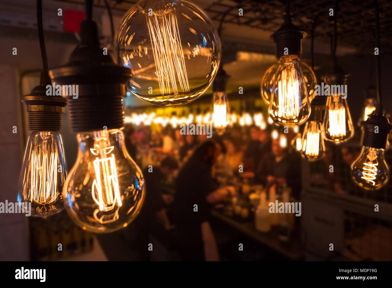 Gruppe der unkenntlich Jugendliche während einer Party an der Bar in einem improvisierten Lager Umwelt, dass eine Schule, Gebäude mit stilvollem Glühbirnen Dekoration im Vordergrund. Stockbild