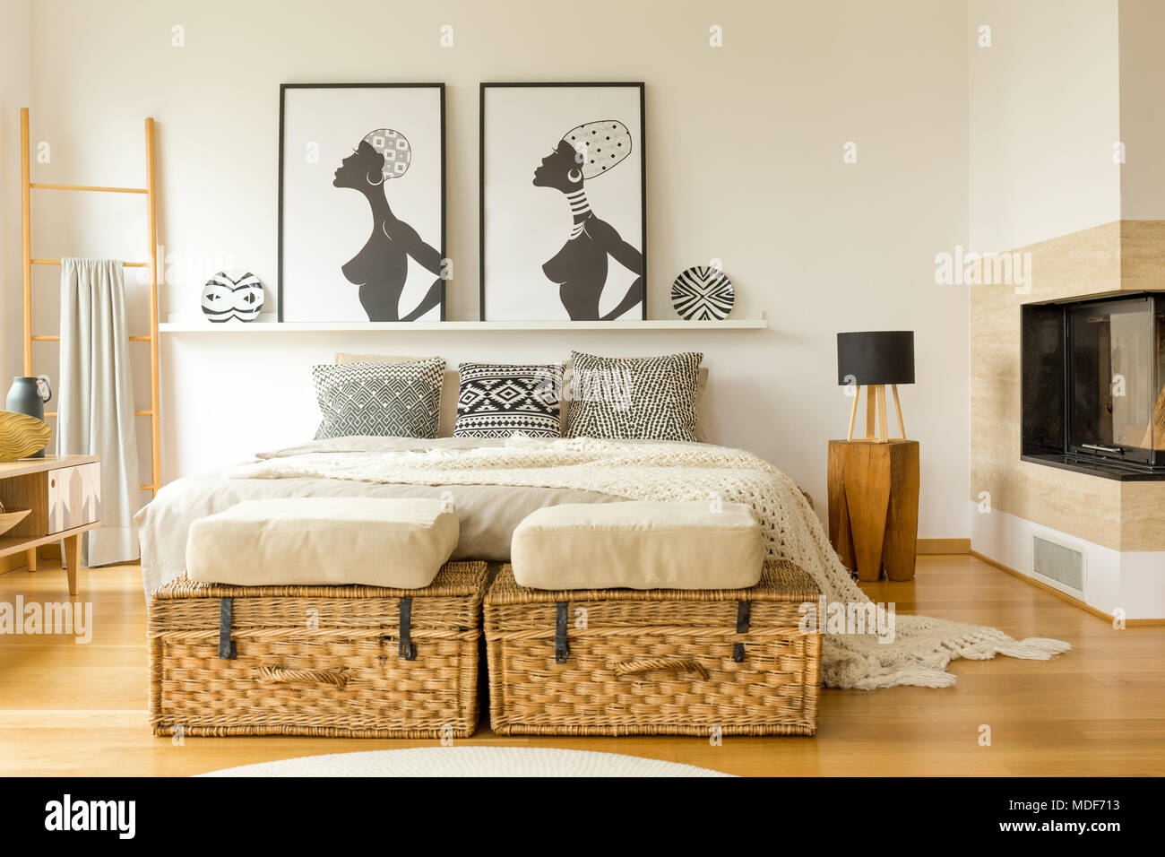 Afrikanische Plakate, wicker Boxen, Kamin und Doppelbett mit ...
