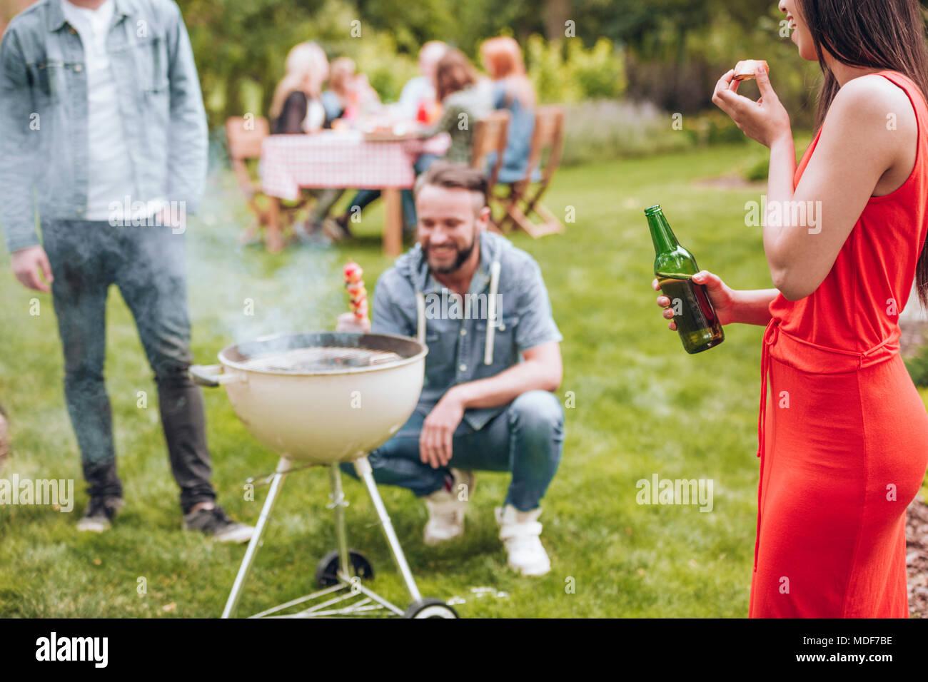 Lächelnde Mädchen trinken Bier im Freien, man grillen ein schaschlik und Freunde an dem Tisch im Hintergrund sitzen Stockbild