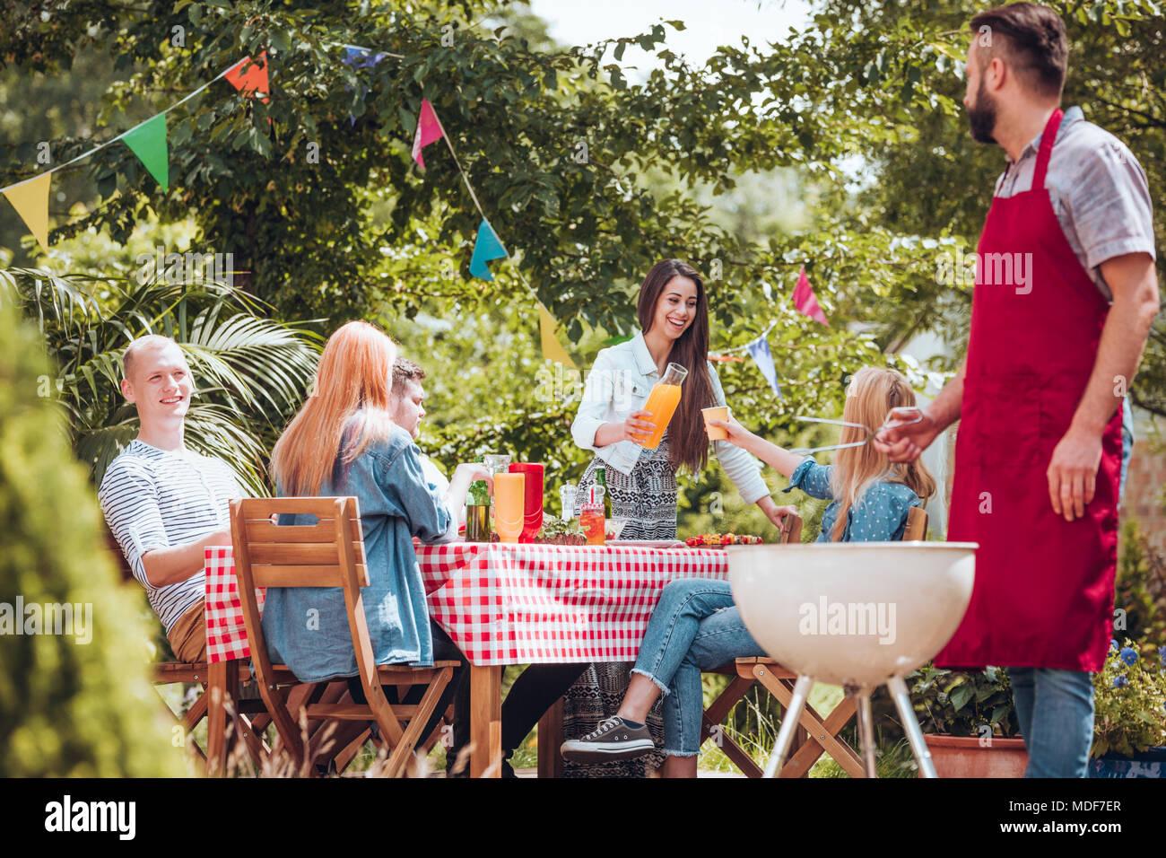 Gruppe von Fröhlichen Freunden feiern und gemeinsam Grillen im Garten Stockbild