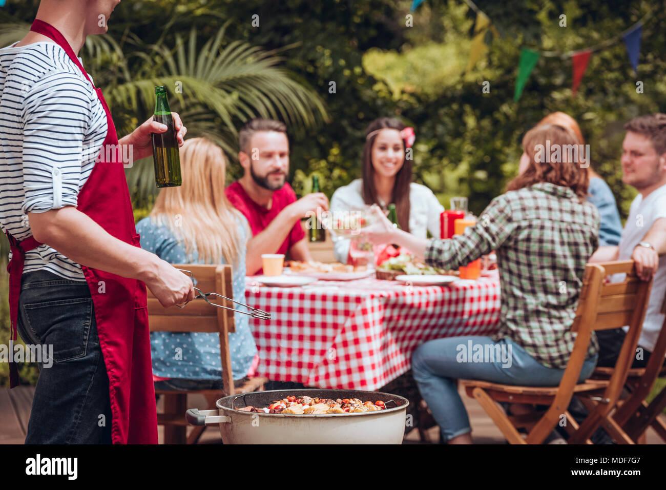 Mann in eine Schürze grillen und Bier trinken, während seine Freunde Essen an einem Tisch im Garten Stockbild
