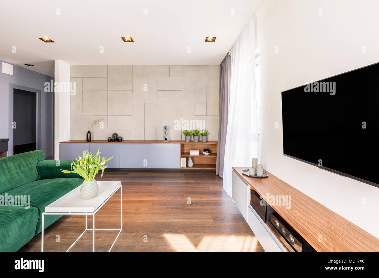 Großer Fernseher In Luxuriösen Wohnzimmer Einrichtung Mit Gelben Tulpen Auf  Weißem Kaffee Tisch Neben Einem Grünen Couch