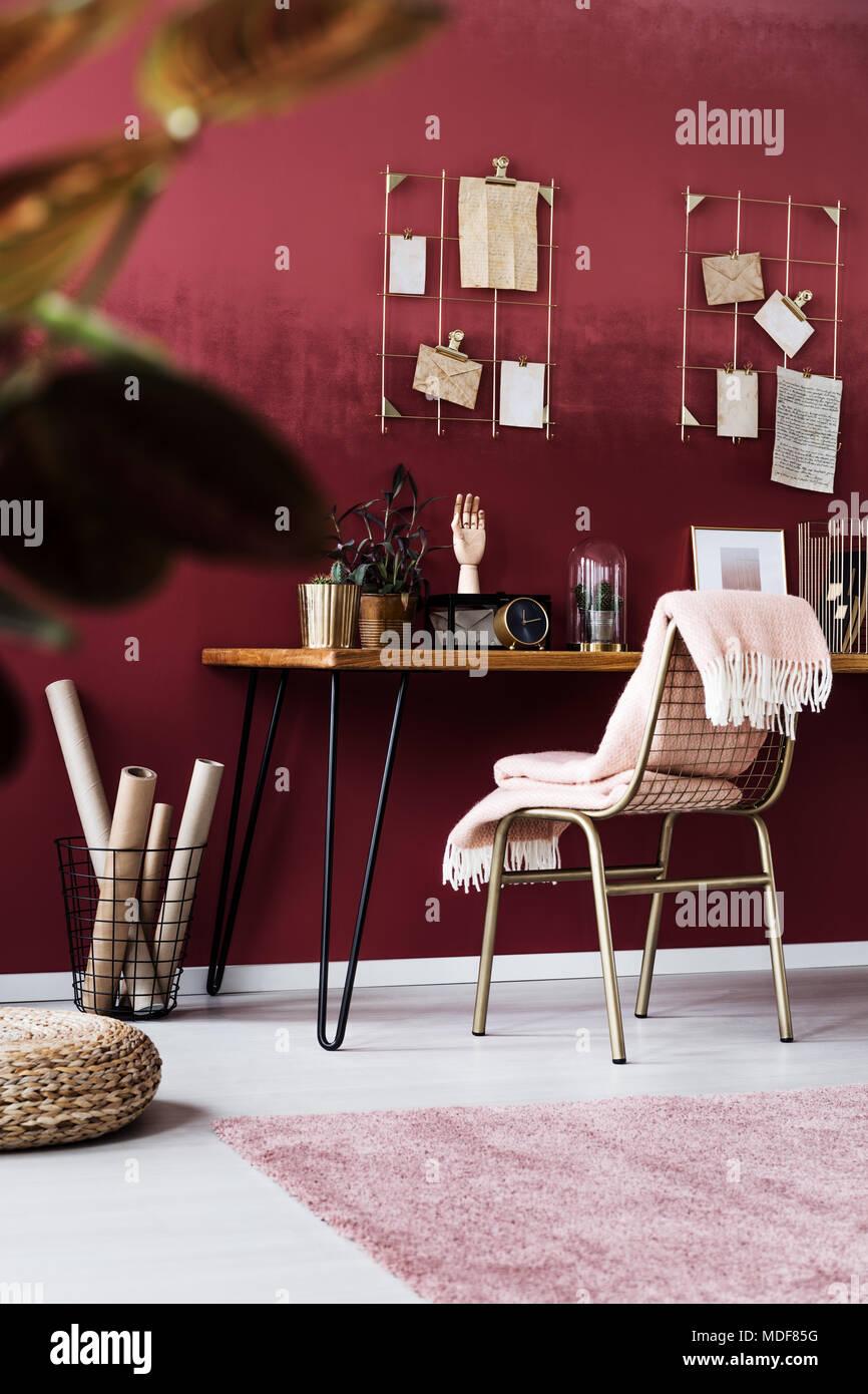 Decke auf Gold Stuhl am Schreibtisch aus Holz mit Uhr in femininen, rosa Home Office Interior Stockbild