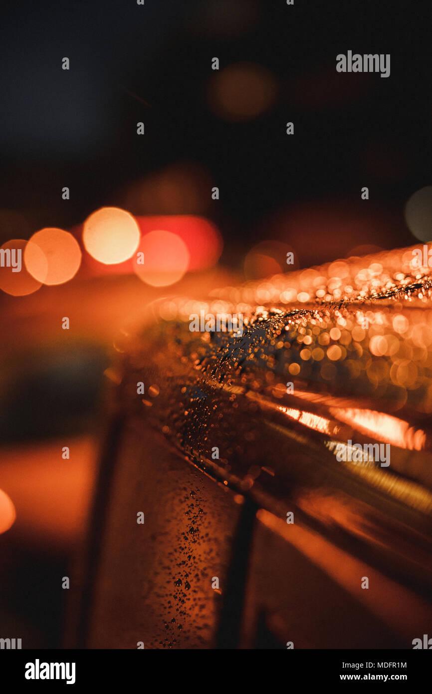 Regentropfen reflektiert Straßenlaternen auf einem geparkten Auto Stockbild
