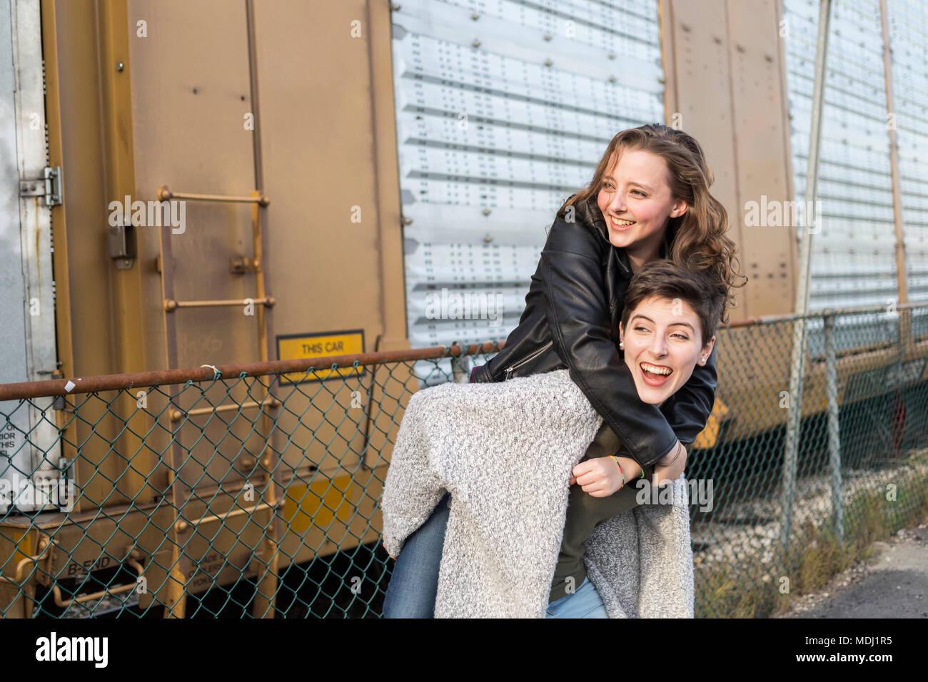 Zwei junge Frauen, die in einem spielerischen Pose neben einem Zug Auto; New Westminster, British Columbia, Kanada Stockbild