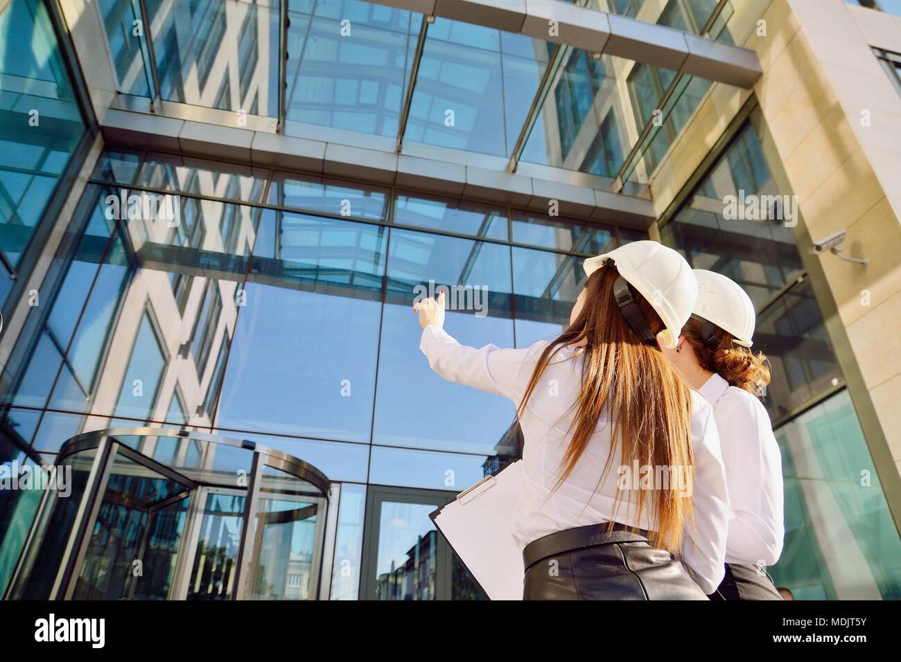 Mädchen in Gebäude weiße Helme mit Tabletten in die Hände auf dem Hintergrund einer Glas Bürogebäude. Frauen sind Ingenieure. Weibliche Berufe. Stockbild