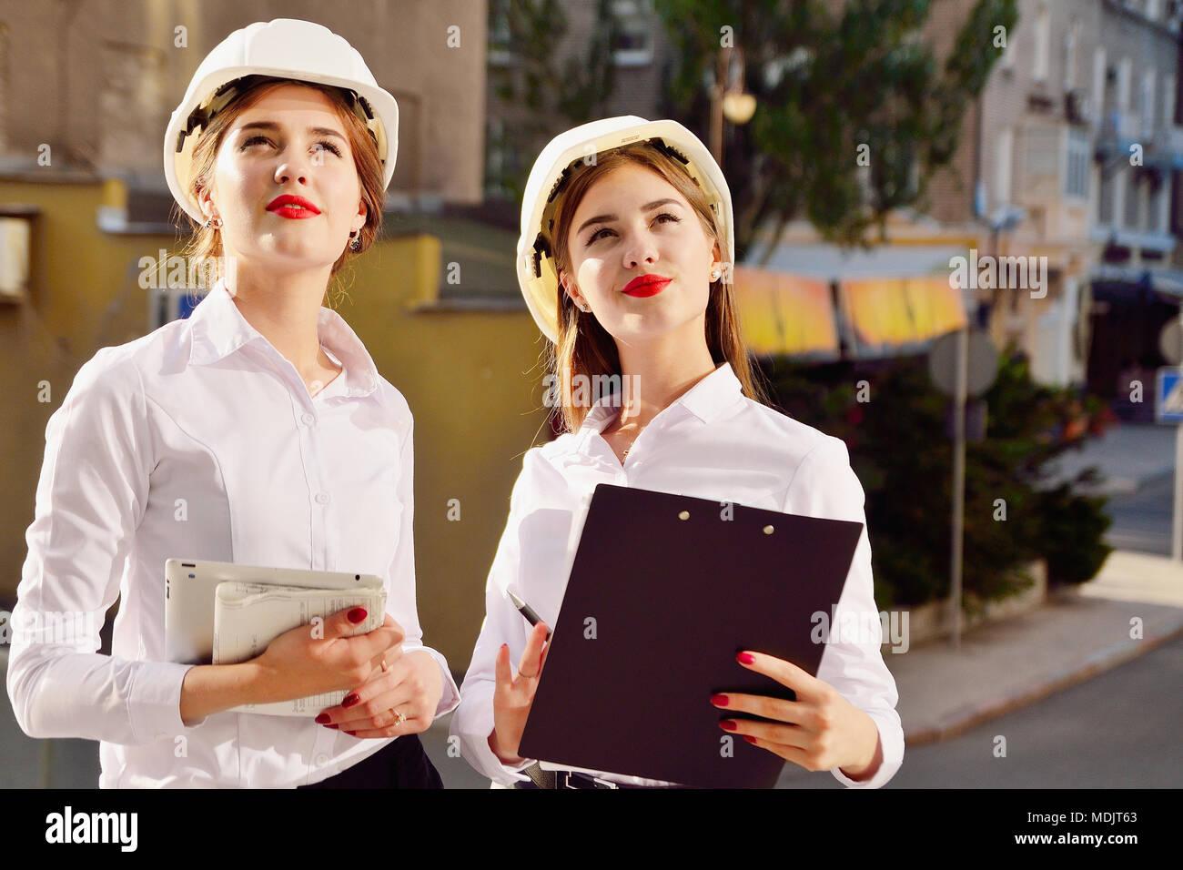 Mädchen in Gebäude weiße Helme mit Tabletten in die Hand. Frauen sind Ingenieure. Weibliche Berufe. Stockbild