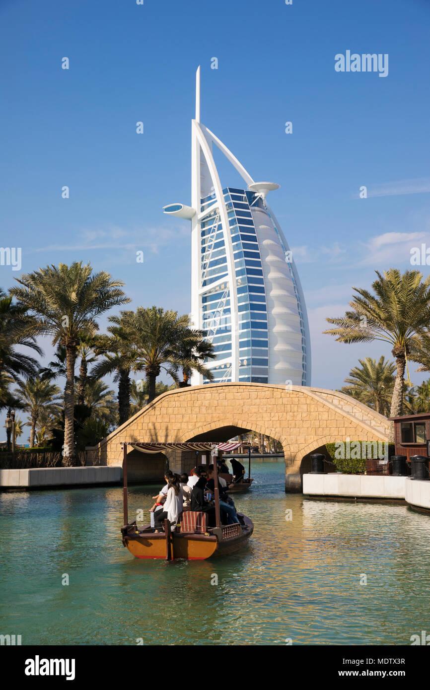 Touristen reiten auf einem Abra auf den Wasserstraßen der Madinat Jumeirah mit dem Burj Al Arab, Dubai, Vereinigte Arabische Emirate, Naher Osten Stockbild