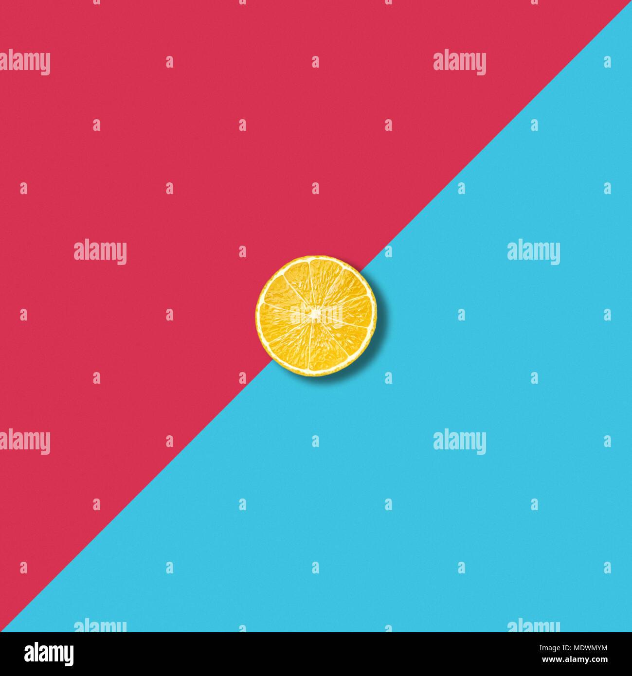 Minimalistische abstrakte Abbildung mit einer Zitronenscheibe am pulsierenden rot und türkis Hintergrund Stockbild