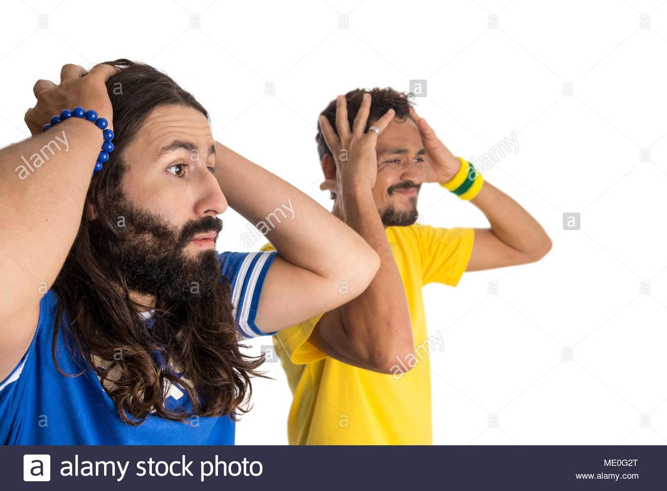 Besorgt, Foul. Brasilien Unterstützer. Zwei brasilianischen Freunde feiern auf Soccer/Football Match auf weißem Hintergrund. Brasilien Farben. Stockbild