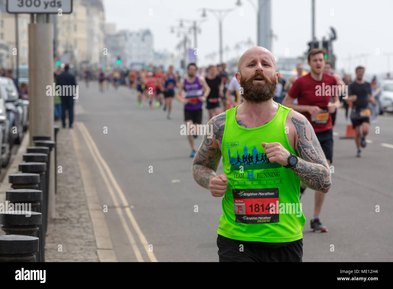 Brighton, Sussex, UK, 15. April 2018; Mann mit Tätowierungen und Bart in Brighton Marathon Stockbild