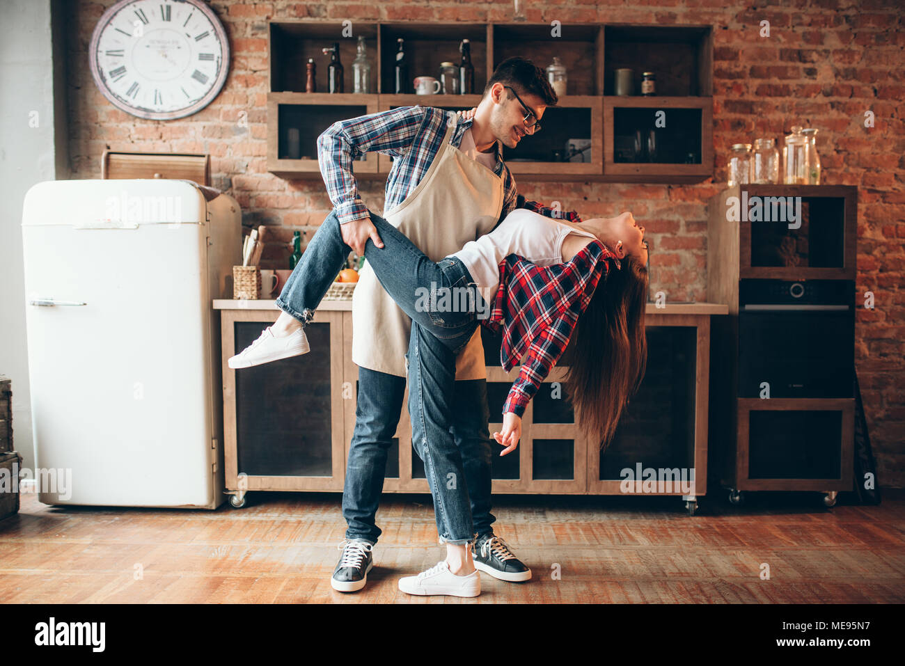 Verspielte Liebe paar Posen auf der Küche. Mann in Schürze und junge ...