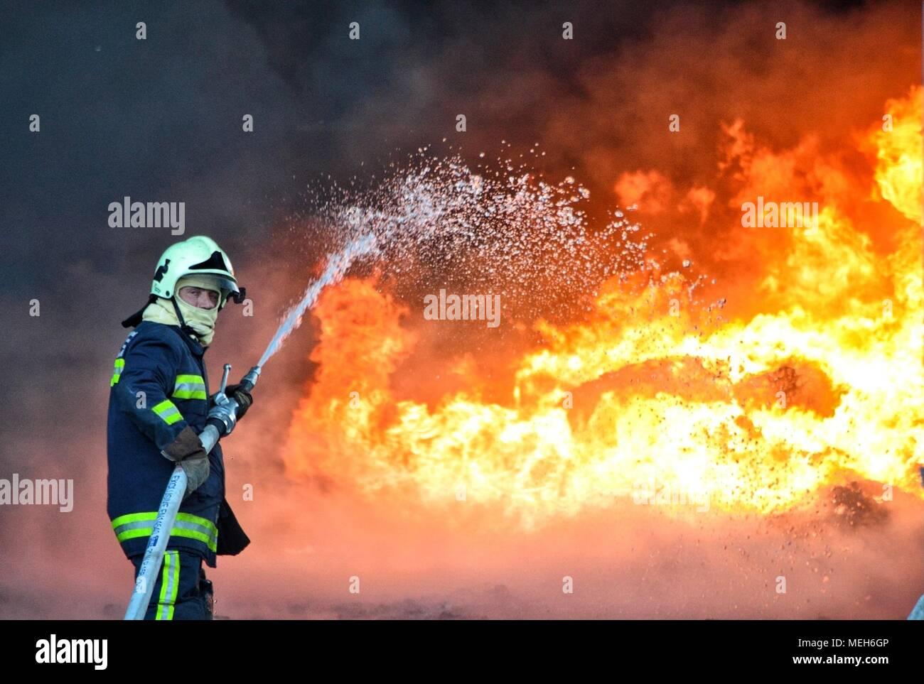Feuerwehrmann kämpft mit Feuer, Feuerwehr auf der Suche nach Überlebenden. Riesige Flammen brannte ein Recyclingunternehmen in Tirana, Feuerwehrmann Löschmittel der Flamme Stockfoto