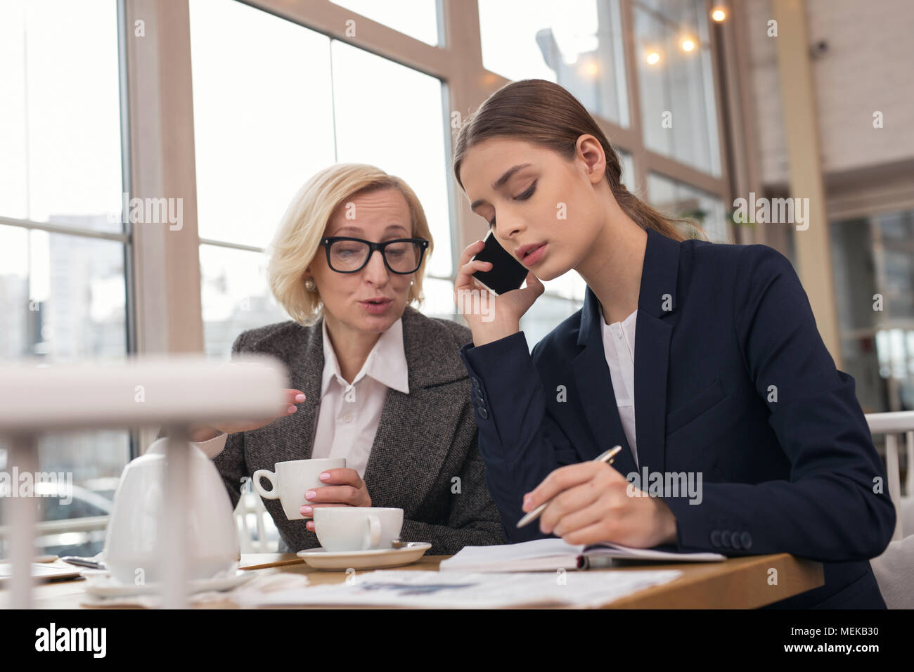 Junge Frau am Telefon zu sprechen konzentriert Stockbild