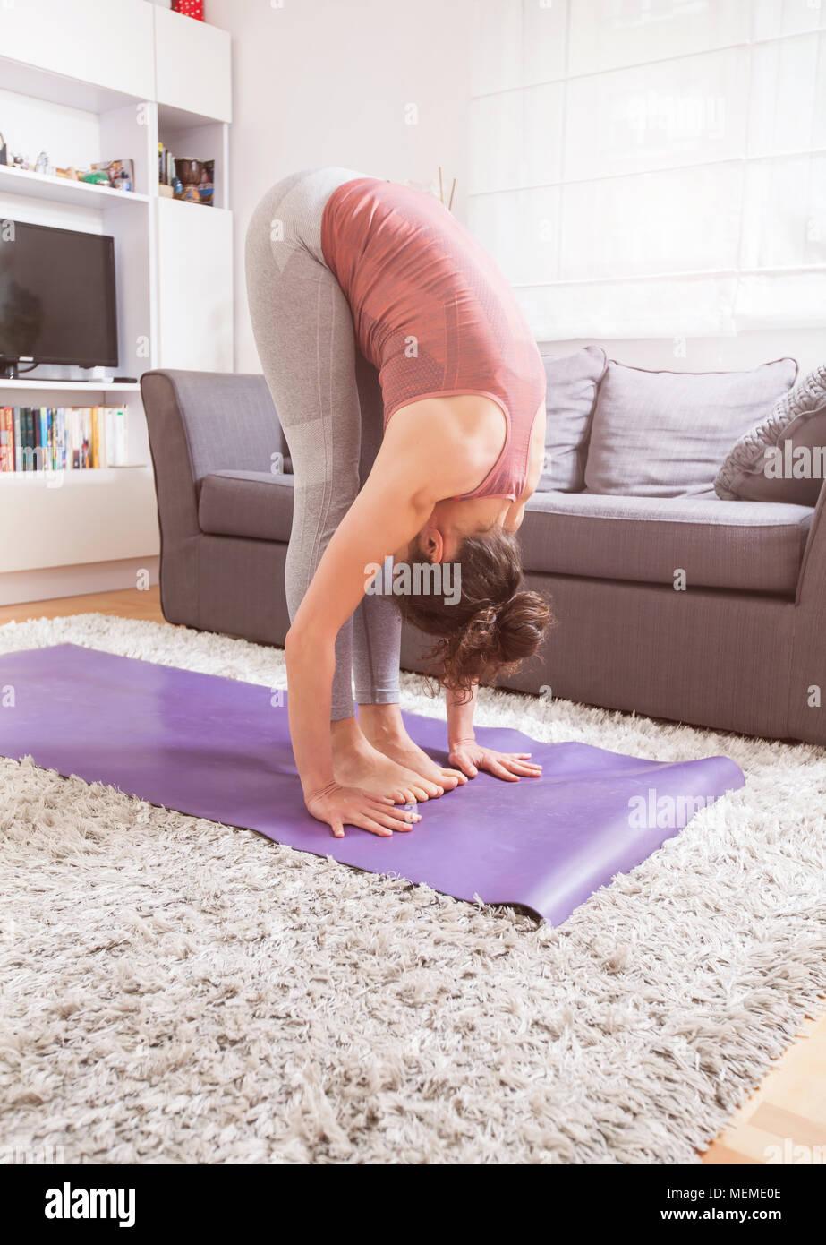 Frau Yoga zu Hause, ständige Biegen, Uttanasana darstellen, innen ...