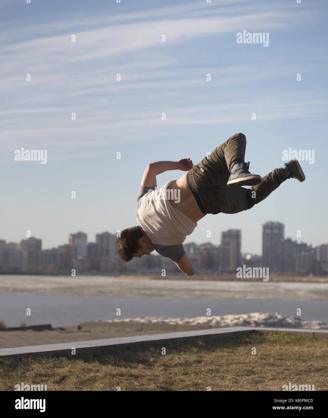 Junger Mann parkour Sportler führt Tricks vor der Skyline Stockbild
