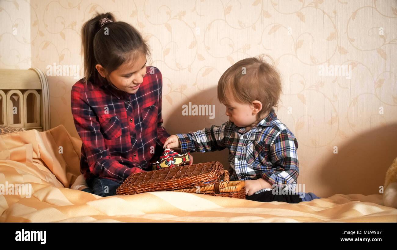 Bett Kleinkind Junge ~ Teenage mädchen spielen mit kleinkind junge auf dem bett im